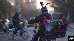 图为一名比萨饼送货员去年12月14日骑车经过北京一交叉路口资料照