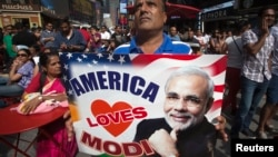 A supporter holds up an America Loves Modi sign as he assembles with a large crowd of people in Times Square to watch the speech by India's Prime Minister Narendra Modi simulcast in New York, Sept. 28, 2014.