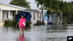 FILE - A woman walks near her flooded neighborhood in Davie, Florida, June 7, 2017. With Hurricane Irma bearing down on Florida, data shows that across the peninsula's 38 coastal counties, just 42 percent of homes in potential hazards zones are insured against flood damage.