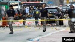 Các nhân viên Cục Điều tra Liên bang (FBI) đi qua những điểm đánh dấu bằng chứng gần hiện trường vụ nổ ở khu phố Chelsea, Manhattan, New York, ngày 18 tháng 9 năm 2016.