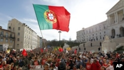 Demonstrators wave a Portuguese flag and shout slogans outside the parliament, at right, during a workers protest, Lisbon, Thursday, March 22, 2012.