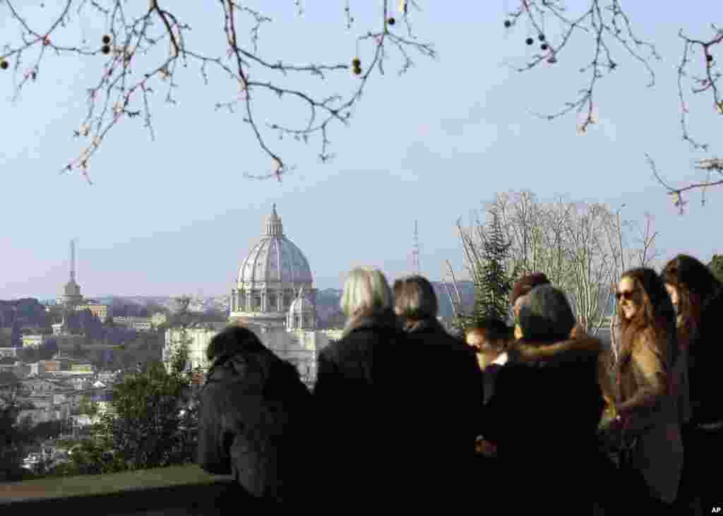 People wait in Rome to see the helicopter taking Pope Benedict to Castel Gandolfo, Feb. 28, 2013.