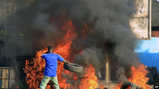 A young man throws a tire onto a fire during a protest by supporters of opposition leader Alassane Ouattara in Abidjan, 03 Dec 2010