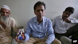 پاکستانی طالبہ کے والد اپنی بیٹی کی تصویر صحافیوں کو دکھا رہے ہیں۔