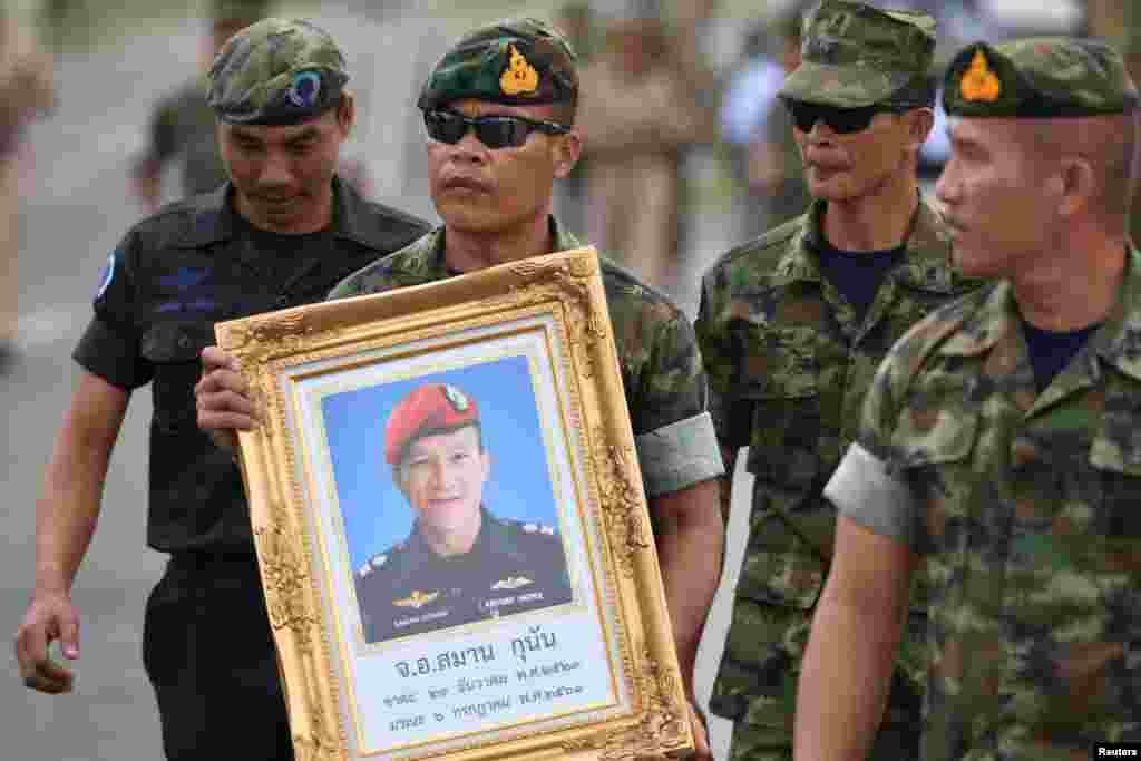 An honor guard hold up a picture of Samarn Poonan, 38, a former member of Thailand's elite navy SEAL unit who died working to save 12 boys and their soccer coach trapped inside a flooded cave as family members weep at a airport, in Rayong province, Thaila