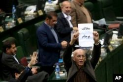 "Iranian conservative lawmaker Bijan Nobaveh Vatan holds up a paper with writing in Persian reading, ""Opponent of the JCPOA,"" in an open session of parliament while discussing a bill on the deal, in Tehran, Iran, Oct. 11, 2015."