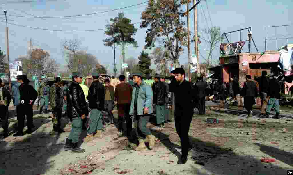 Afghan police forces and civilians inspect the site of a suicide attack in Maimana, Faryab province, Afghanistan, March 18, 2014.
