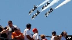 Para penonton menyaksikan atraksi udara 4 pesawat jet L-39 Albatros pada pembukaan acara balap 'Indianapolis 500', Minggu (25/5).
