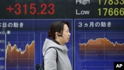 A woman walks by an electronic stock board of a securities firm in Tokyo, Feb. 1, 2016. Chinese stocks fell Monday after a weak manufacturing report. Other markets were mixed.