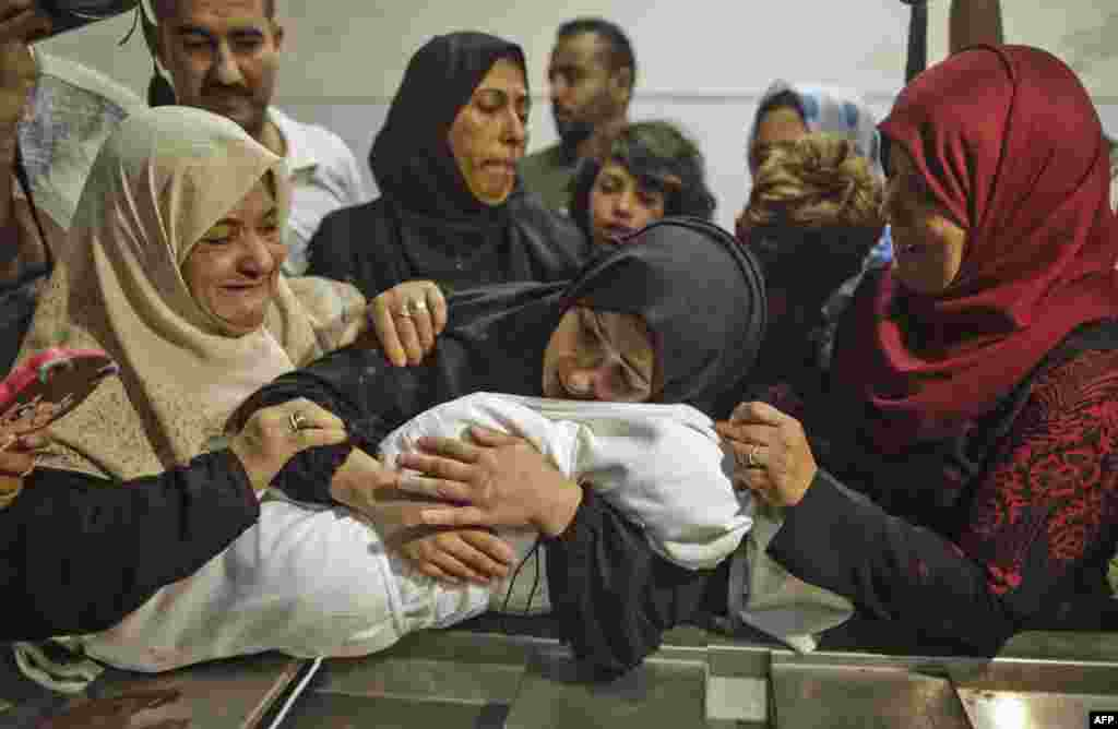 The mother of a Leila al-Ghandour (C), a Palestinian baby of 8 months who according to Gaza's health ministry died of tear gas inhalation during clashes in East Gaza the previous day, holds her at the morgue of al-Shifa hospital in Gaza City. Israeli forces killed 59 Palestinians during clashes and protests along the Gaza border against the U.S. embassy opening in Jerusalem on May 14, 2018.
