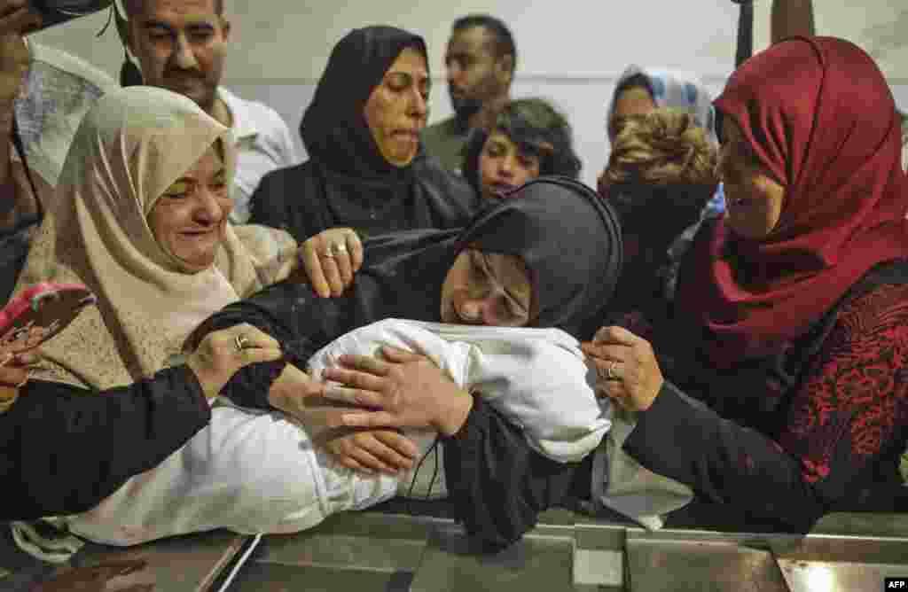 Ibu dari bayi Leila al-Ghandour (tengah), bayi Palestina usia8 bulan yang meninggal akibat menghirup gas air mata pasukan Israel saat terjadi bentrokan di Gaza, memeluk jenazah putrinya di rumah sakit Shifa, Gaza City, Jalur Gaza.