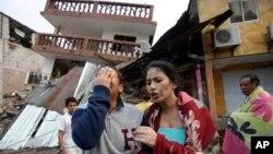 에콰도르 지진 피해지역인 페데르날레스의 주민들이 17일 무너진 집 앞에서 눈물을 흘리고 있다.