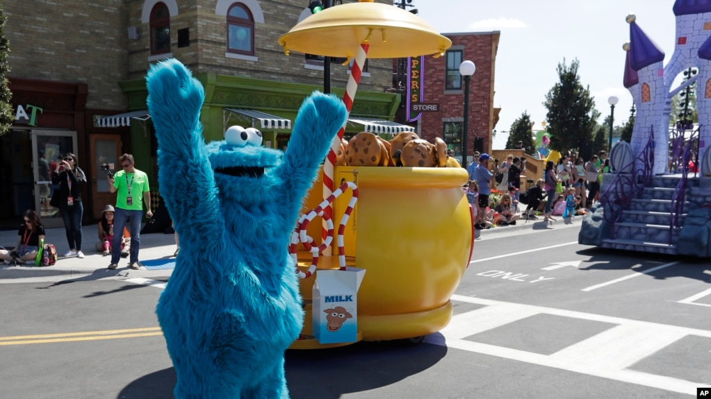 In this 2019 photo, Cookie Monster dances around his cookie jar at SeaWorld Orlando's opening of Sesame Street land in Orlando, Florida. (AP Photo/John Raoux)