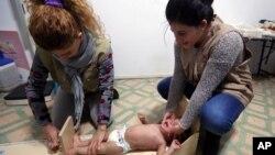 Ảnh tư liệu cho thấy nhân viên cứu trợ người tị nạn Syria đo chiều cao của một em bé tại phòng khám y tế ở Bekaa Valley, Libăng ngày 11/3/2014.