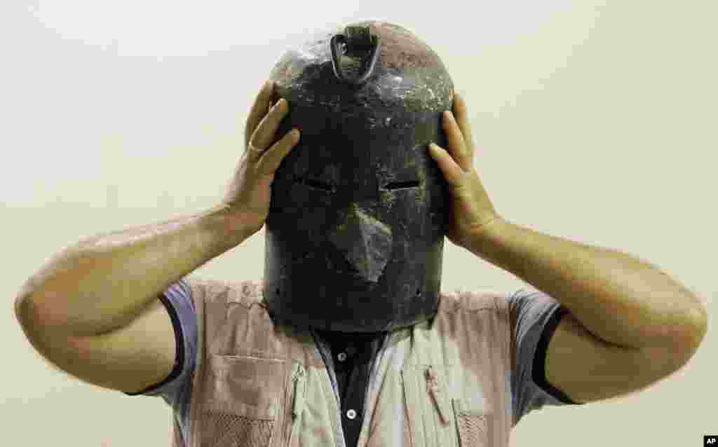 An Iraqi man wears a metal mask used as a torture device by the regime of Iraq's ousted leader Saddam Hussein at the Shaheed Monument in Baghdad, Iraq.