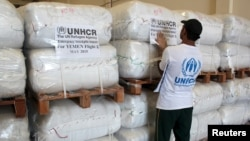 A UNHCR employee arranges aid at the Dubai International Humanitarian city in Dubai, United Arab Emirates, before shipping them to Yemen, May 14, 2015.