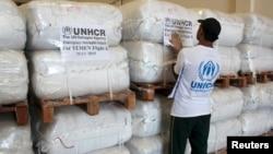 A UNHCR employee arranges aid at the Dubai International Humanitarian city in Dubai, United Arab Emirates, before shipping them to Yemen, May 14, 2015.