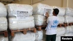 FILE - A UNHCR employee arranges aid at the Dubai International Humanitarian city in Dubai, United Arab Emirates, before shipping it to Yemen, May 14, 2015.