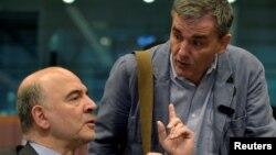 24일 벨기에 브뤼셀에서 열린 유로존 재무장관 회의에서 그리스 채무 삭감 문제가 논의된 가운데, 피에르 모스코비치 유럽연합 경제담당 집행위원(왼쪽)이 유클리드 차칼로토스 그리스 재무장관과 대화하고 있다.