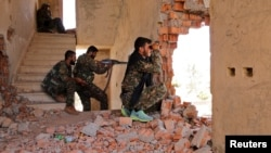 FILE - Kurdish People's Protection Units (YPG) fighters take up positions inside a damaged building in al-Vilat al-Homor neighborhood in Hasaka city, as they monitor the movements of Islamic State fighters.