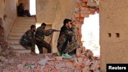 Kurdish People's Protection Units (YPG) fighters take up positions inside a damaged building in al-Vilat al-Homor neighborhood in Hasaka city, as they monitor the movements of Islamic State fighters, July 22, 2015.