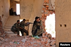 FILE - Kurdish People's Protection Units (YPG) fighters take up positions inside a damaged building in al-Vilat al-Homor neighborhood in Hasaka city, as they monitor the movements of Islamic State fighters stationed in Ghwayran neighborhood.