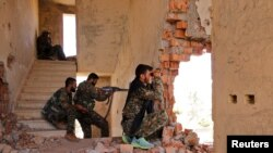 FILE - Kurdish People's Protection Units (YPG) fighters take up positions inside a damaged building in al-Vilat al-Homor neighborhood in Hasaka city, Syria, as they monitor local movements of Islamic State fighters.