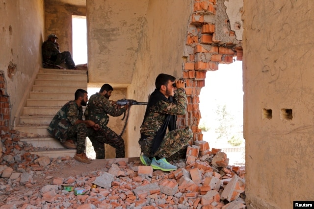 FILE - Kurdish People's Protection Units (YPG) fighters take up positions inside a damaged building in Hasaka city, as they monitor the movements of Islamic State fighters in 2015.