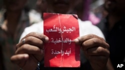 "An Egyptian protester holds a card that says ""army, people and police - one hand"" during an spontaneous demonstration against Egypt's President Morsi in Tahrir Square in Cairo, June 29, 2013."