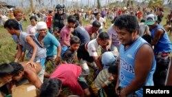 美軍士兵和菲律賓民眾11月17日在菲律賓災區發放救援物資。