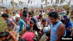 17일 필리핀 태풍 피해 지역인 타클로반 북부의 한 마을에서, 주민들이 미군 헬리콥터에서 투하한 생수를 줍고 있다.