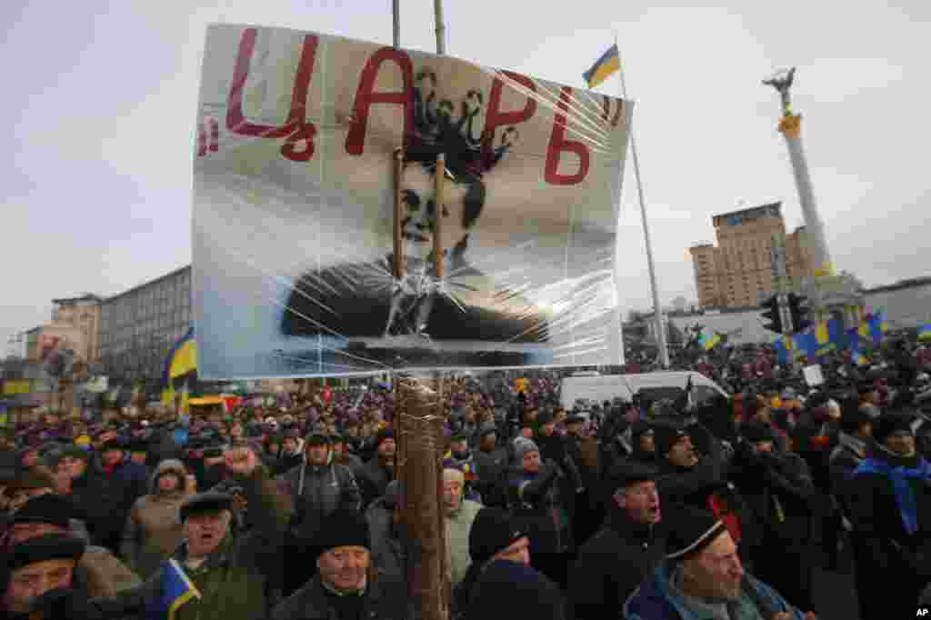 "Protesters hold a poster with a portrait of President Viktor Yanukovych that reads ""tsar"" as they rally in Independence Square in Kyiv, Dec. 3, 2013."