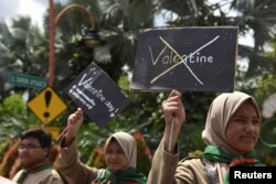 Muslim students hold posters during a protest against Valentine's Day celebrations in Surabaya, Indonesia, Feb. 13, 2017, in this photo taken by Antara Foto.