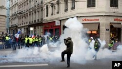 Demonstrators run away through tear gas in Lyon, central France, Dec. 15, 2018.