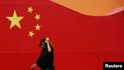 FILE - A woman wearing a mask walks past a wall painted with China's national flag in central Beijing.