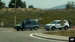 Imagen tomada de la televisión que muestra un vehículo de la policía atravesado en una calle de Trebes, al sur de Francia, cerca de donde se desarrolla una toma de rehenes.