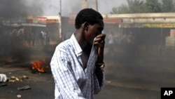 25일 수단 카드로에서 시민이 연기를 막으려 입을 가리고 있다.