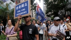 Protesters hold placards and wave Hong Kong colonial flags during the annual pro-democracy protest in Hong Kong. As the Asian financial center prepares for legislative elections in September, a new wave of radical political activists are planning to join the campaign, including some who advocate the once-unthinkable idea of independence from China, July 1, 2016.