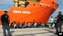리비아 인근 해안에서 구조된 난민 8백여 명이 8일 이탈리아에 도착한 뒤 줄을 서 기다리고 있다.