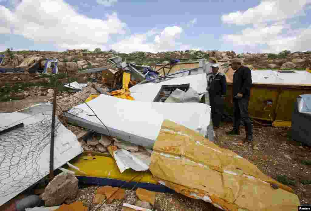 Những người Palestine đứng nhìn những gì còn lại của một dự án trường học được tài trợ bởi Viện trợ Nhân đạo và Bảo vệ Dân sự của Ủy hội châu Âu và bị phá hủy bởi lực lượng của Israel, ở Khirbet Tana gần thành phố Nablus thuộc Bờ Tây.
