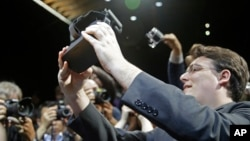 FILE - Oculus founder Palmer Luckey holds up the new Oculus Rift virtual reality headset for photographers following a news conference, in San Francisco, June 11, 2015.