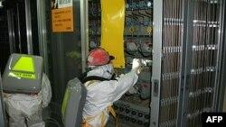 Các công nhân mặc đồ bảo hộ kiểm tra tình trạng mực nước ở khu vực nhiên liệu bên trong nhà máy điện hạt nhân bị hư hại Fukushima Daiichi, ngày 10 tháng 5, 2011