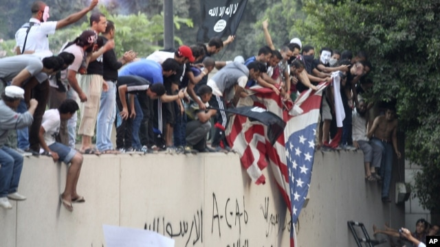 Protesters destroy an American flag pulled down from the U.S. Embassy in Cairo, Egypt, Sept. 11, 2012