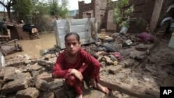 Bé gái Pakistan ngồi trên đống đổ nát của căn nhà sau các trận mưa lớn ở Nowshera, gần Peshawar, ngày 22/8/2012