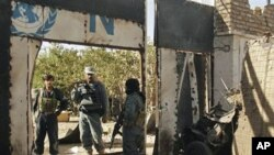 ກຳລັງຮັກສາຄວາມສະຫງົບອັຟການິສຖານ ຢືນຢູ່ປະຕູທາງເຂົ້າ ສຳນັກງານ ສປຊ ທີ່ເມືອງ Herat ໃກ້ໆກັບຊາກລົດລະເບີດສະລະຊີບ (23 ຕຸລາ 2010)