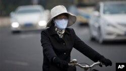 Una ciclista usa una máscara en Pekín para protegerse de la contaminación atmosférica.