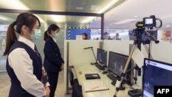 台湾疾病控制中心的工作人员在台北桃园国际机场检测从中国武汉抵达的乘客的体温。(2020年1月13日)