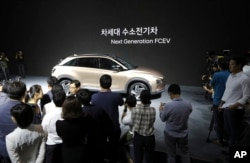 Hyundai Motor Co.'s new hydrogen fuel cell vehicle is surrounded by members of media during a media preview in Seoul, South Korea, Thursday, Aug. 17, 2017. (AP Photo/Lee Jin-man)