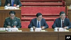 China's Guangdong Province Party Secretary Wang Yang (R) smiles next to China's Vice Premier Zhang Dejiang (C) and Vice Chairman of China's Central Military Commission Xu Caihou attend the second plenary meeting of the National People's Congress at the Gr