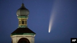 The comet Neowise or C/2020 F3 is seen behind an Orthodox church over the Turets, Belarus, 110 kilometers (69 miles) west of capital Minsk, early Tuesday, July 14, 2020. (AP Photo/Sergei Grits)